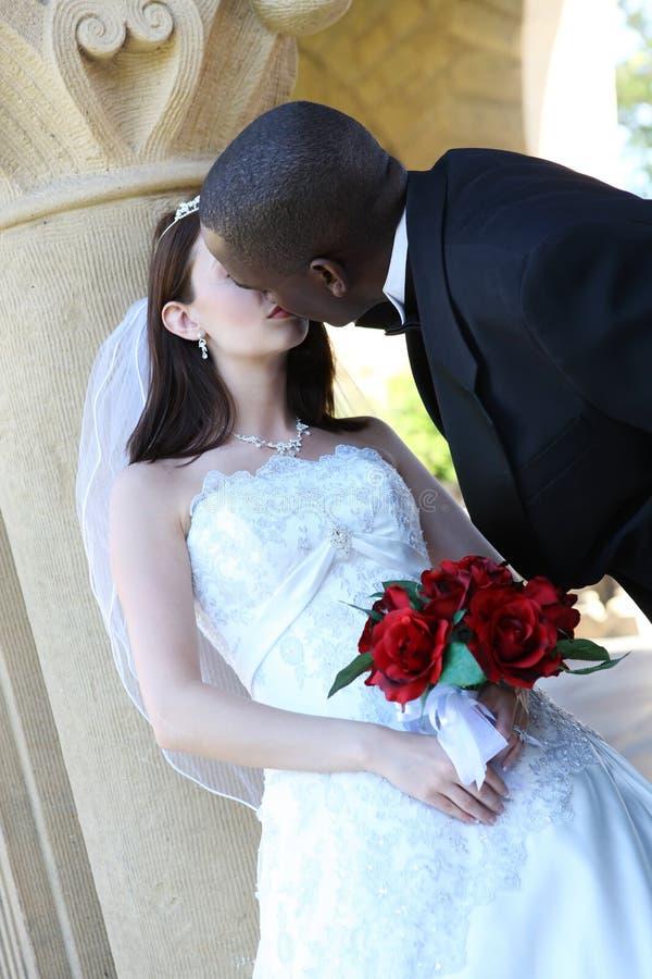 夫妇人种间亲吻的婚礼 免版税库存照片