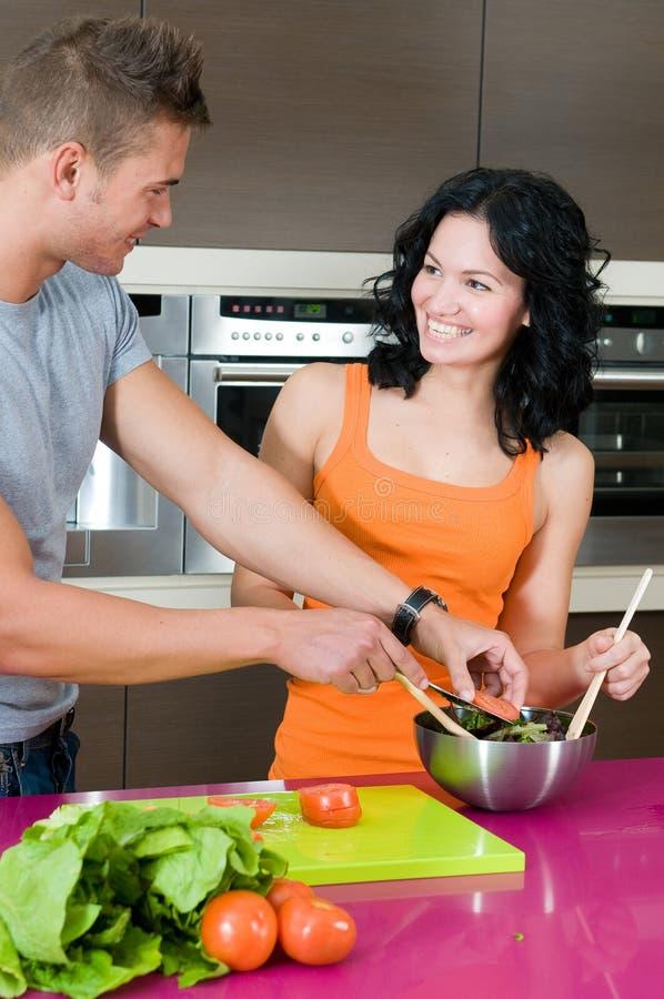 夫妇他们厨房的沙拉 免版税库存照片