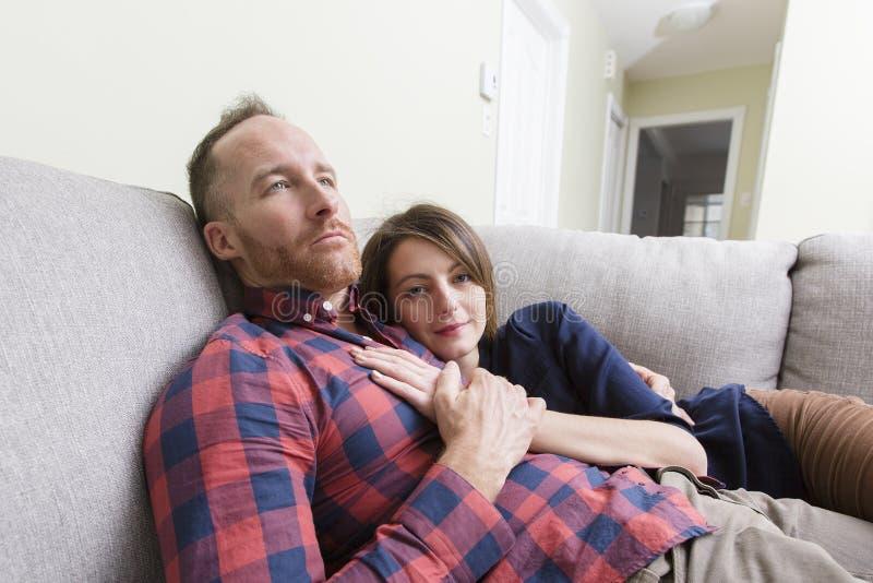 夫妇位于的沙发年轻人 图库摄影