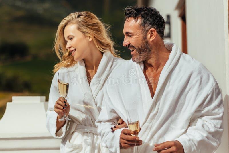 夫妇佩带的浴巾在阳台上 库存图片