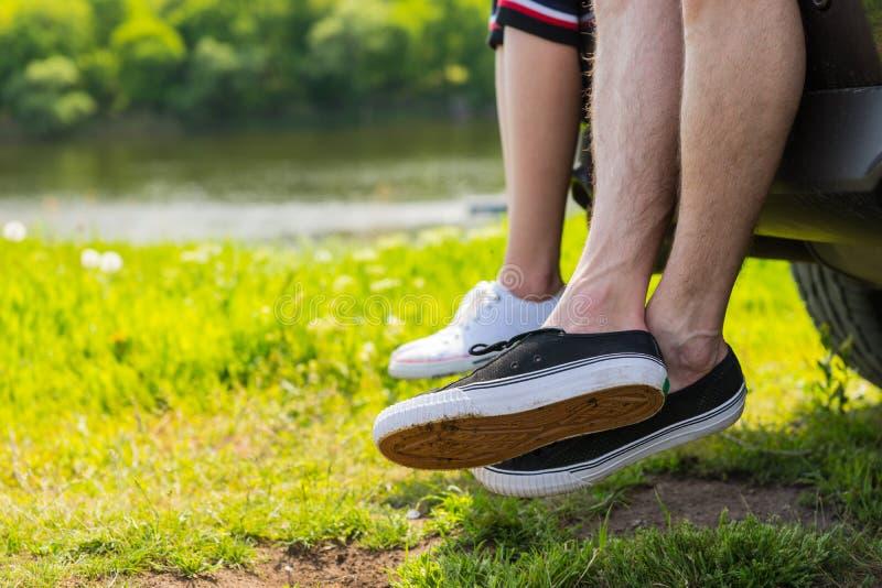 夫妇佩带的运动鞋坐汽车车辆后档板  免版税库存照片