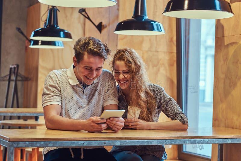 夫妇使用一种数字式片剂的愉快的年轻学生,当坐在桌在学院军用餐具在断裂期间时 免版税库存图片