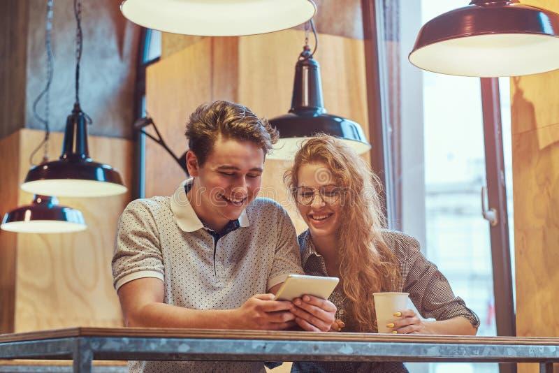 夫妇使用一种数字式片剂的愉快的年轻学生,当坐在桌在学院军用餐具在断裂期间时 库存照片