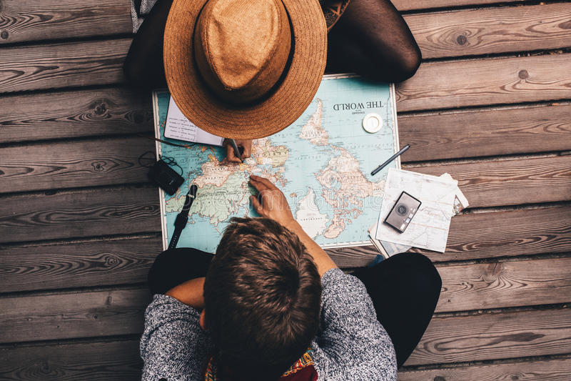 夫妇使用世界地图的计划假期 免版税库存照片