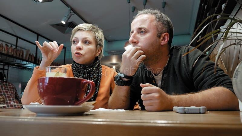 夫妇供以人员,并且妇女在咖啡馆餐馆吃谈话 免版税库存照片