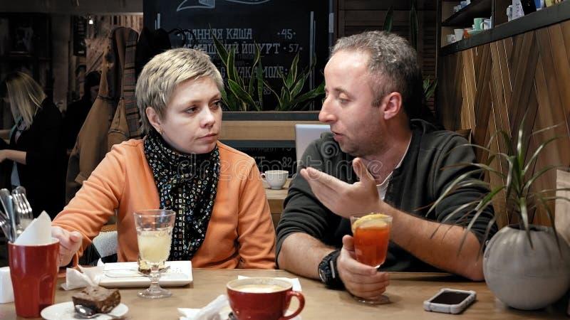 夫妇供以人员,并且妇女在咖啡馆餐馆吃谈话 库存照片