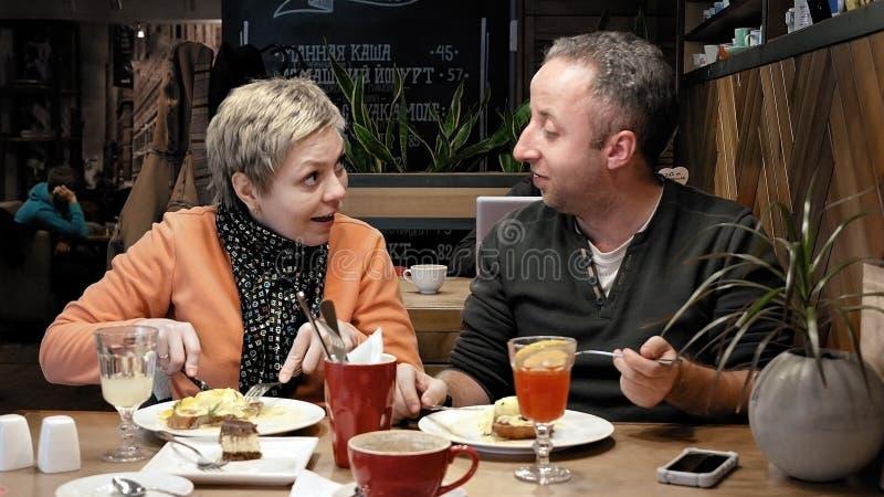 夫妇供以人员,并且妇女在咖啡馆餐馆吃谈话 免版税库存图片