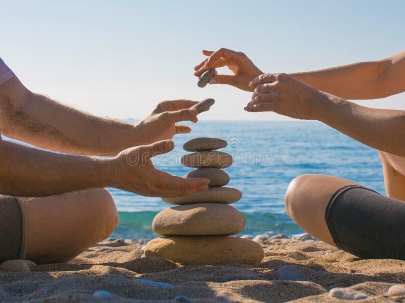 夫妇修造在海滩的一座石金字塔 关系和爱概念 免版税库存图片