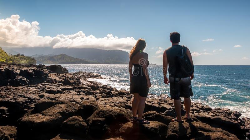 夫妇俯视海洋在离岩石考艾岛海岸的附近 免版税库存照片