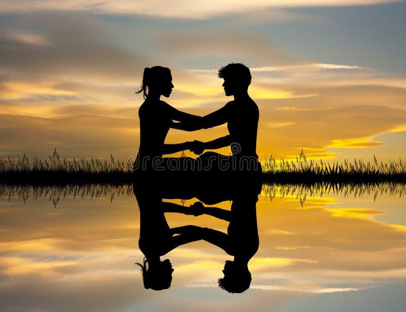 夫妇做在河岸的瑜伽在日落 免版税图库摄影
