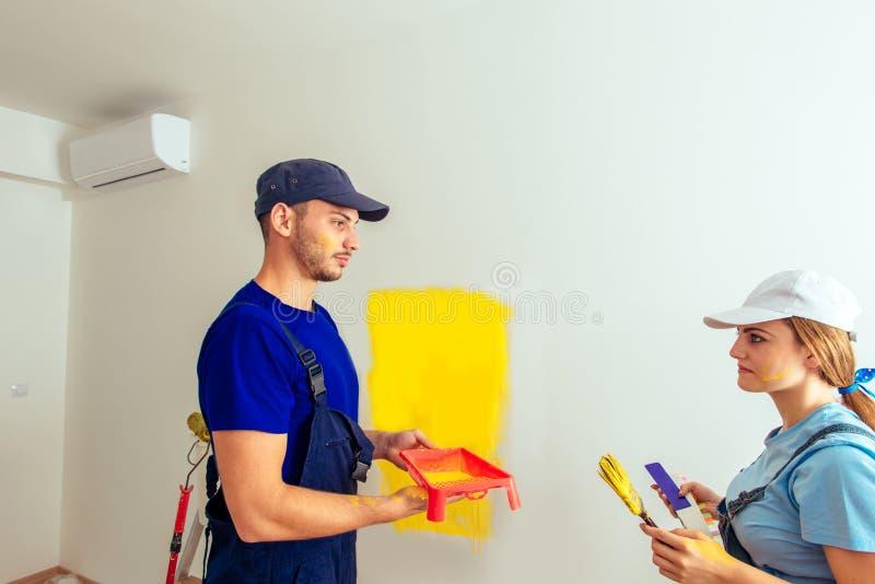 夫妇做着在家修理和绘有油漆刷的墙壁 库存照片