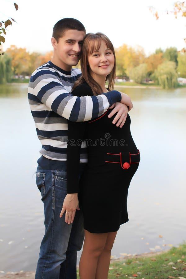 夫妇停放怀孕的年轻人 免版税库存照片