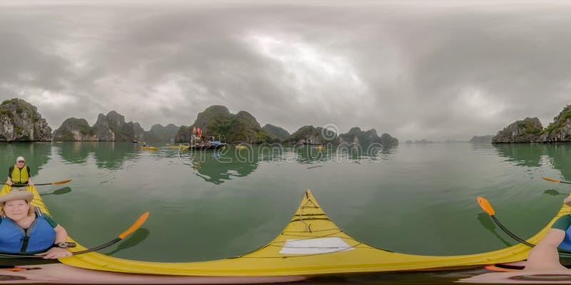 夫妇划皮船的下龙湾,越南 免版税图库摄影