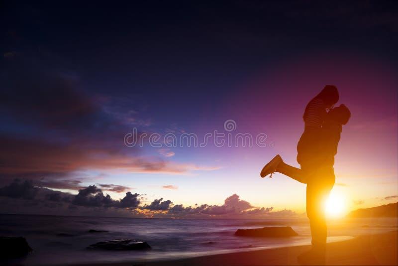 年轻夫妇剪影在拥抱在海滩的爱的 库存照片