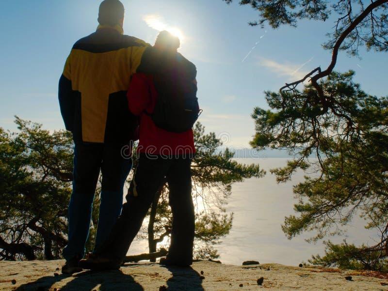 夫妇剪影 在冬天步行的年轻对反对太阳 库存照片