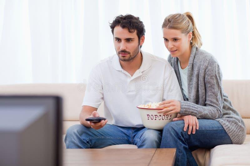 夫妇吃玉米花电视注意 库存图片