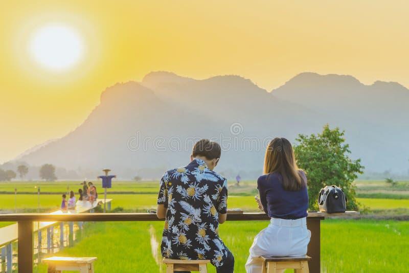 夫妇后面看法坐在休息的和等待的时刻为在农夫的阳台的日落照相 免版税库存照片
