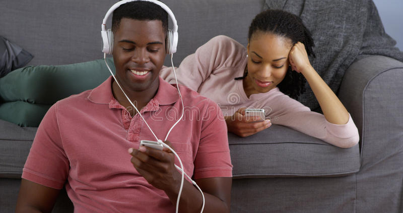 年轻黑夫妇听音乐和使用巧妙的电话 免版税库存照片