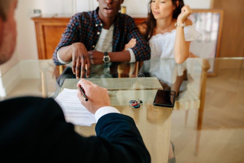夫妇和房地产经纪商谈论在物产期间成交 免版税库存照片