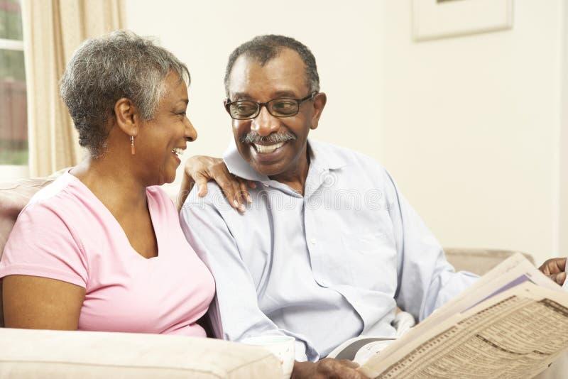 夫妇回家报纸读取前辈 库存照片