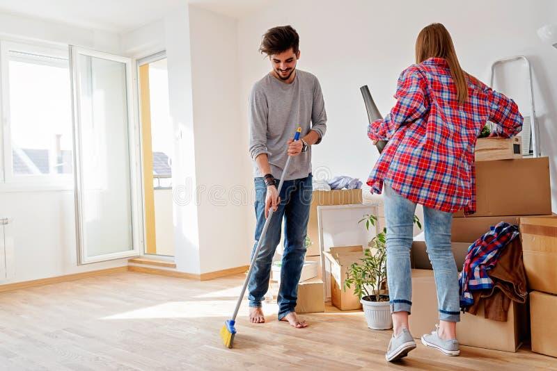 夫妇回家移动新的年轻人 打开箱子容器和清洗 免版税库存图片