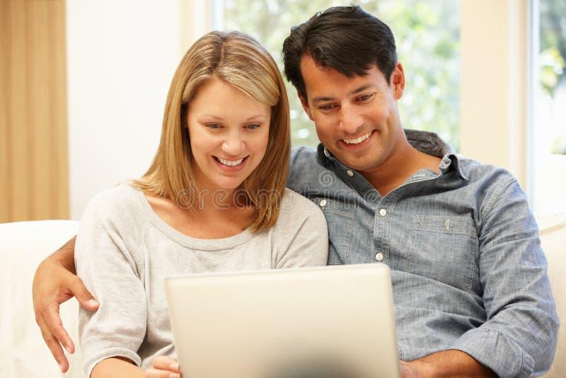 夫妇回家膝上型计算机使用 免版税图库摄影
