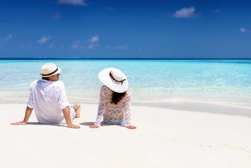 夫妇在一个热带海滩放松在马尔代夫 免版税库存照片