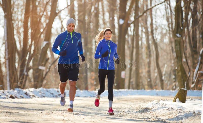夫妇在一起跑本质上的冬天 免版税库存照片
