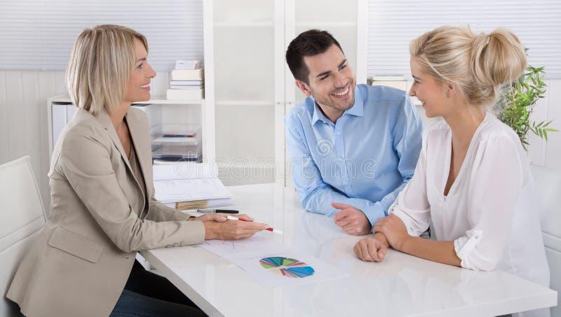年轻夫妇在与一位银行家或顾问的一个日期退休的a 库存照片