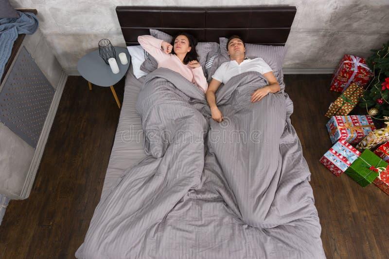 年轻夫妇在与p的圣诞树附近叫醒佩带的睡衣 免版税图库摄影
