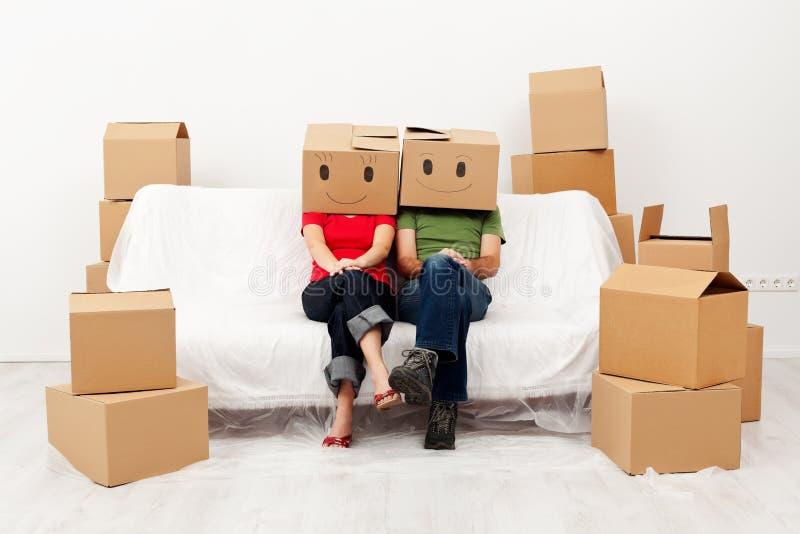 夫妇在他们有纸板箱的新的家 免版税库存照片
