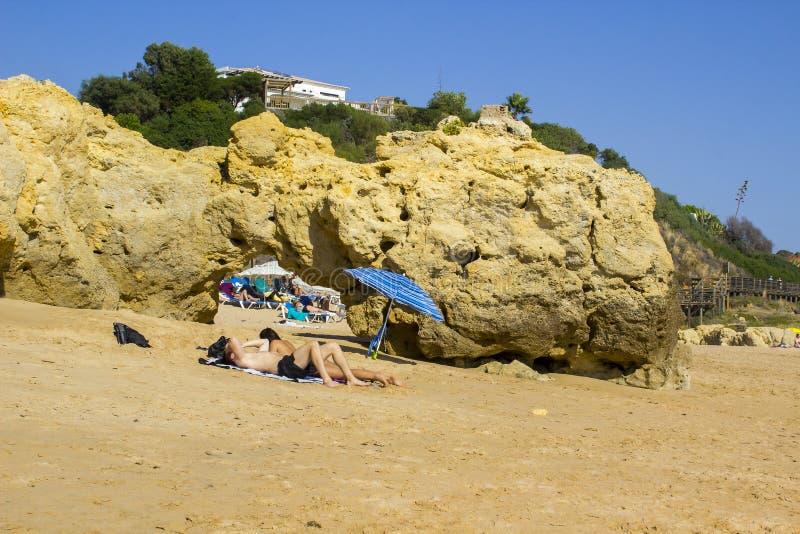 夫妇在伞的树荫下坐一个海滩在葡萄牙 库存照片