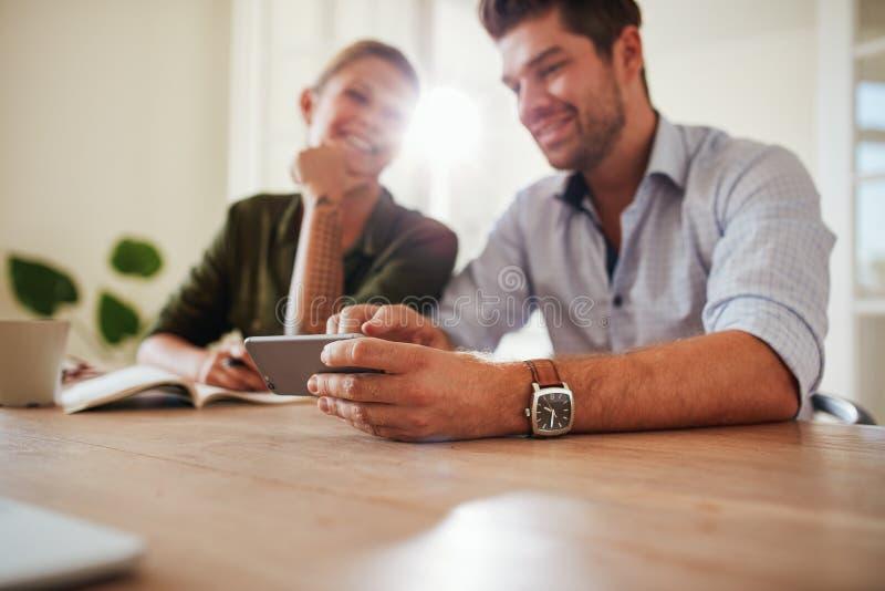 年轻夫妇在使用手机的桌上在家 库存图片
