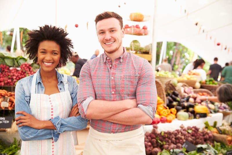 夫妇在农夫新鲜的食品批发市场的赛跑摊位 库存照片