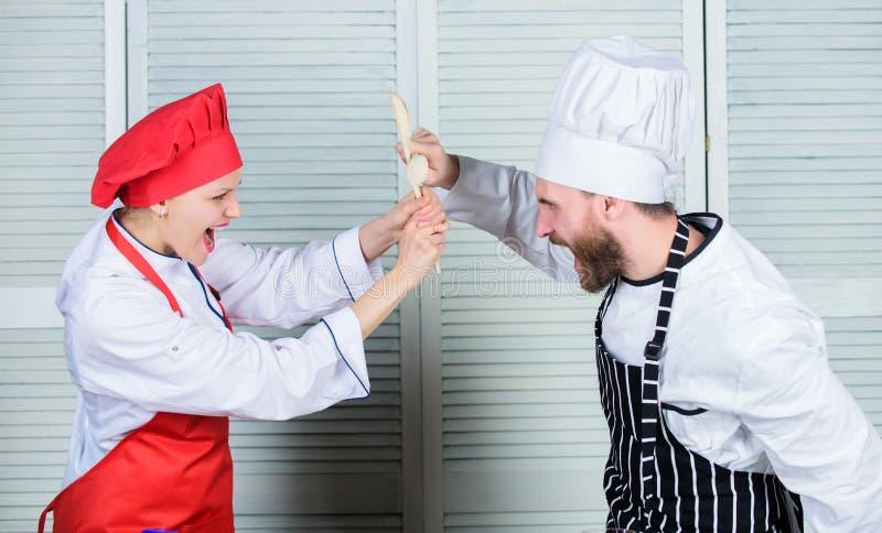 夫妇在厨房艺术竞争 厨房规则 谁更好烹调 烹饪争斗概念 的妇女和烹饪有胡子的人 图库摄影