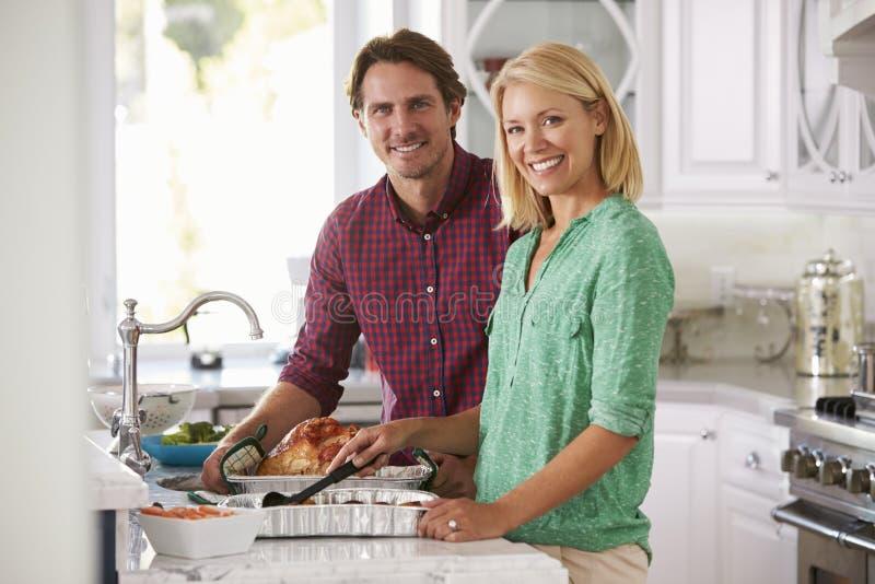 夫妇在厨房里一起做烘烤土耳其膳食 免版税库存图片