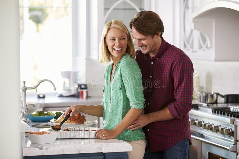 夫妇在厨房里一起做烘烤土耳其膳食 图库摄影