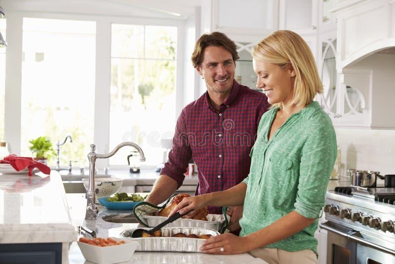 夫妇在厨房里一起做烘烤土耳其膳食 库存照片
