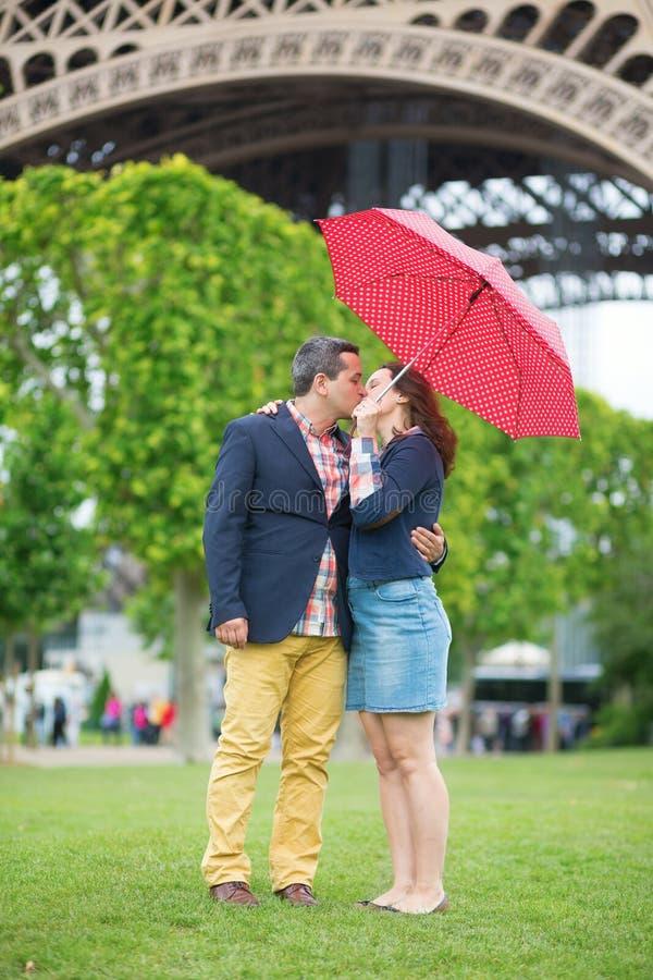 夫妇在埃佛尔铁塔附近的伞下 免版税库存图片