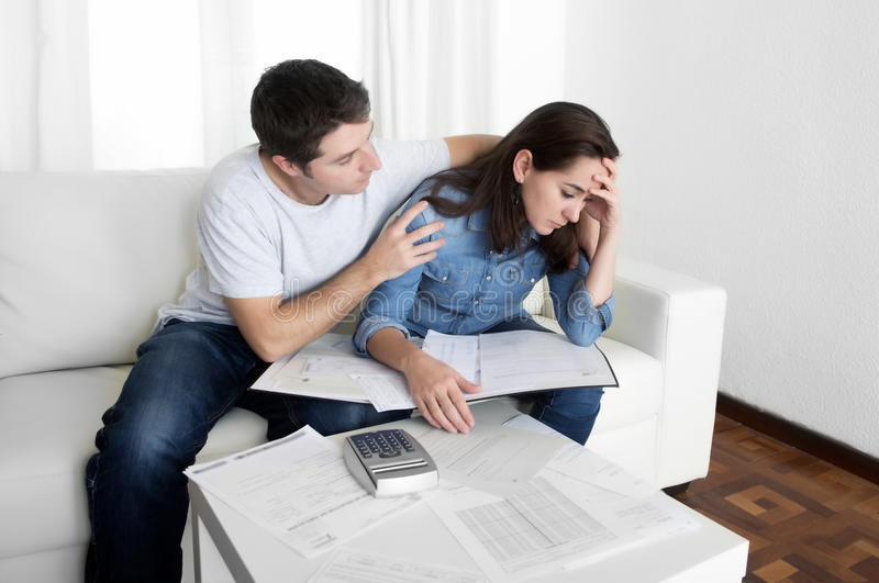 年轻夫妇在安慰财政问题的重音丈夫担心在家妻子 免版税图库摄影