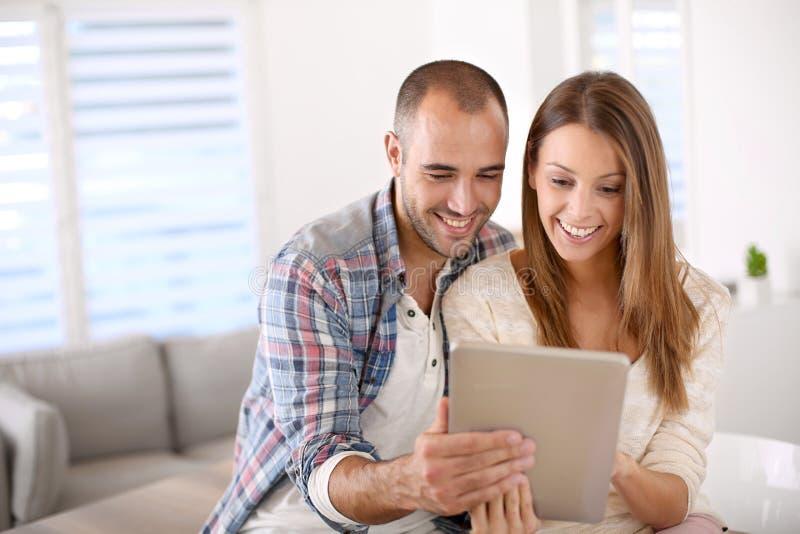 年轻夫妇在家使用片剂 免版税库存照片