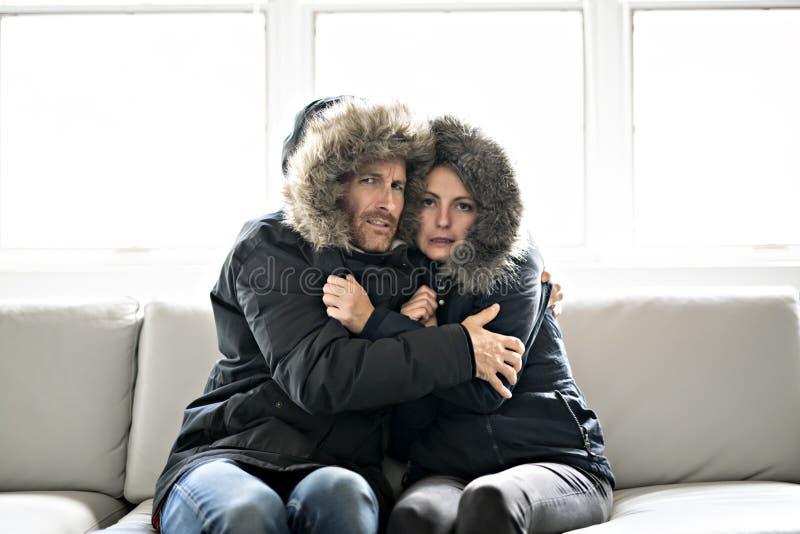 夫妇在家有在沙发的寒冷有冬天外套的 库存图片