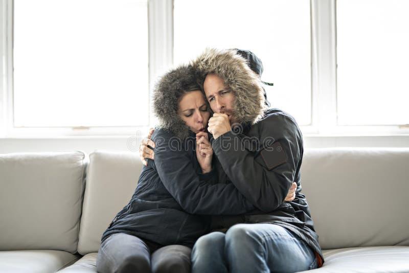 夫妇在家有在沙发的寒冷有冬天外套的 免版税图库摄影
