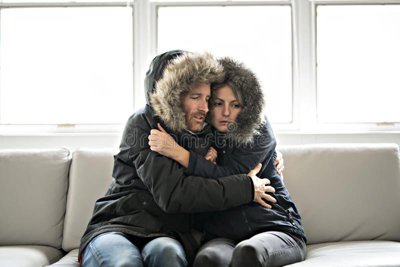 夫妇在家有在沙发的寒冷有冬天外套的 库存照片