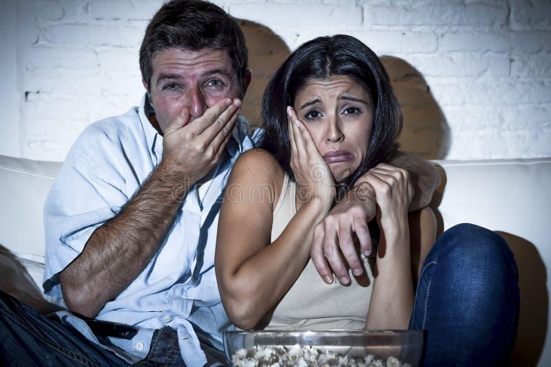 夫妇在家沙发长沙发拥抱观看的电视电影一起 库存照片