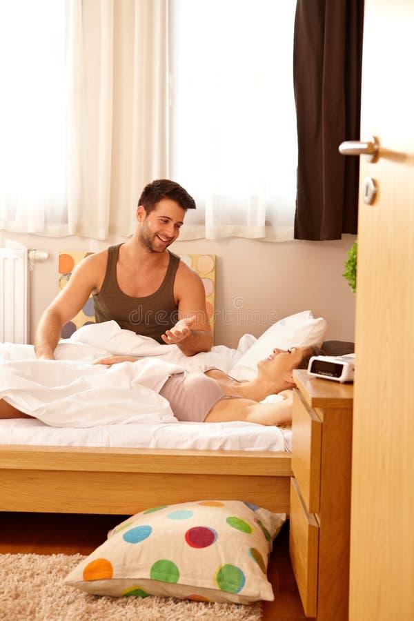 年轻夫妇在床上早晨 免版税库存图片