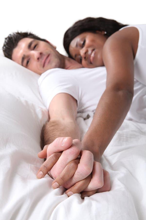 夫妇在床上的握手 免版税库存图片