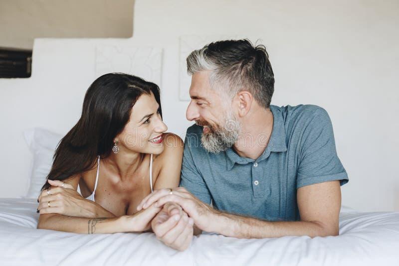 夫妇在床上的花费他们的蜜月 免版税库存照片