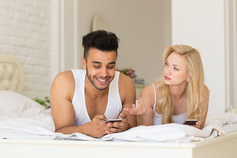 年轻夫妇在床,愉快的使用细胞巧妙的电话的微笑西班牙人上坐被挫败的妇女 免版税库存图片
