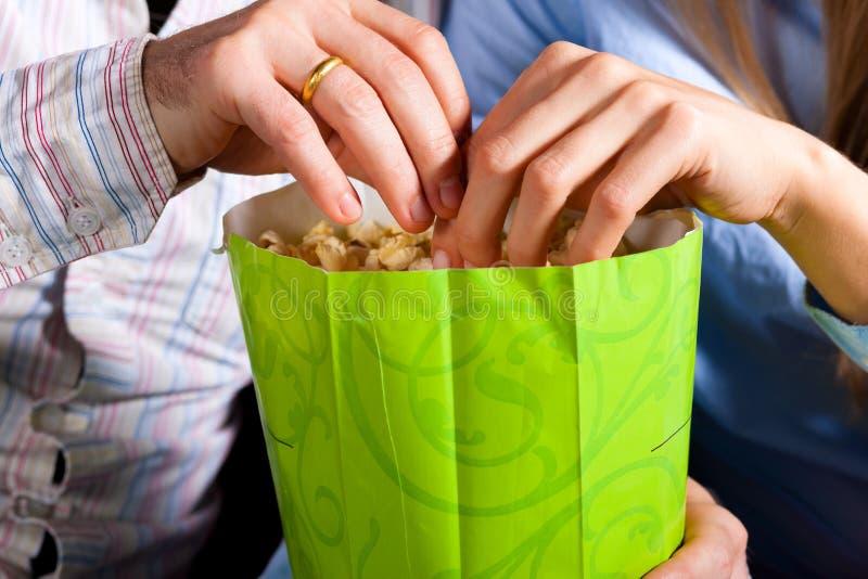 夫妇在戏院剧院用玉米花 库存照片